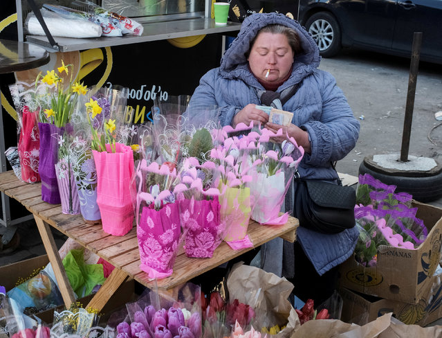 A woman counts her money as she sells flowers ahead of International Women's Day in central Kiev, Ukraine March 7, 2019. (Photo by Gleb Garanich/Reuters)