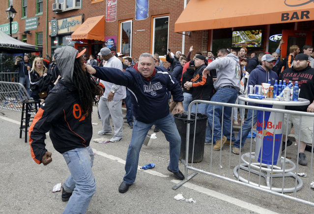 A protestor, left, fights with a bar patron outside of a bar near Oriole Park at Camden Yards after a rally for Freddie Gray, Saturday, April 25, 2015, in Baltimore. (Photo by Patrick Semansky/AP Photo)