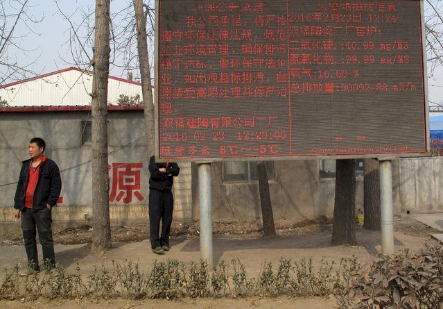 An electronic board displaying pollutant emission levels is seen outside a ceramic tile factory in Linyi, Shandong province, China, February 23, 2016. (Photo by Brenda Goh/Reuters)