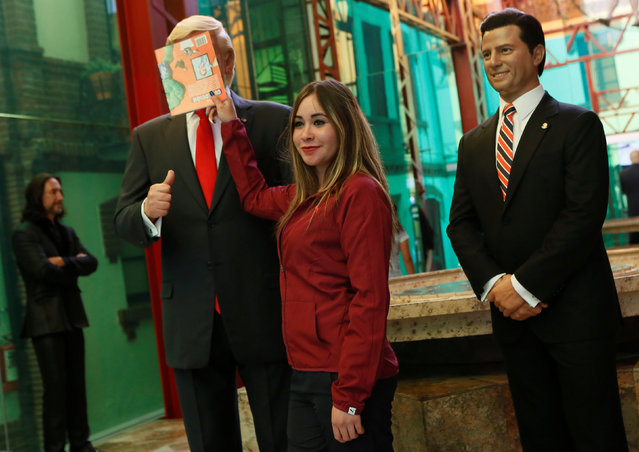 A woman poses as she covers the face of a wax figure of U.S. President Donald Trump next to a wax figure of Mexico's President Enrique Pena Nieto, at the wax museum in Mexico City, Mexico January 30, 2017. (Photo by Henry Romero/Reuters)