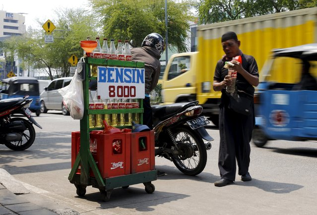 Jajak Rahmat (R), a street seller, holds an empty bottle after serving a customer on Mangga Dua Street in North Jakarta, Indonesia January 29, 2016. Jajak Rahmat buys gasoline from state-owned Pertamina and sells it on the street to motorists for 8,000 rupiah ($0.58) per litre. A dramatic drop in oil prices, driven down by a glut in supply, is translating into a mixed bag for motorists. All countries have access to the same oil prices on international markets, but retail prices vary wildly, largely because of taxes and subsidies. (Photo by Reuters/Beawiharta)