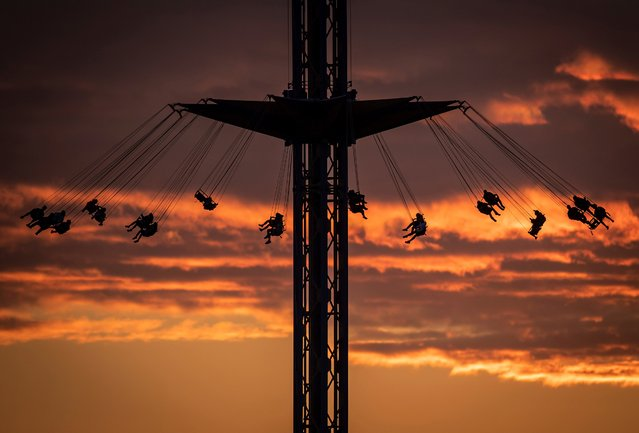 People are silhouetted while riding the Atmosfear double swing, which lifts riders more than 66 meters into the air while spinning at up to 70 km/h, at the Pacific National Exhibition at sunset in Vancouver, British Columbia, on Tuesday, August 31, 2021. (Photo by Darryl Dyck/The Canadian Press via AP Photo)
