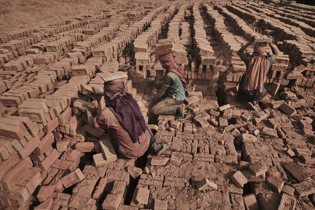 Two kiln workers sift through a seemingly endless pile of bricks in Kathmandu Valley, Nepal, 20 March 2016. (Photo by Jan Moeller Hansen/Barcroft Images)