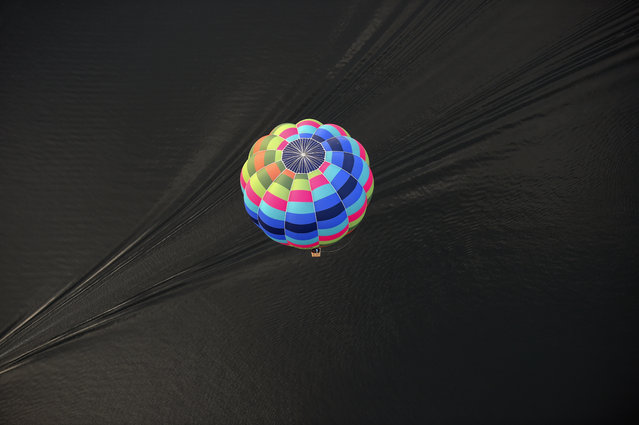 A hot air balloon is seen flying over Lake Burley Griffin at the Canberra Balloon Festival in Canberra, Australia on March 14, 2016. This year marks the 30th anniversary of the Canberra Balloon Festival considered one of the biggest hot air balloon festivals in the world. (Photo by Lukas Coch/EPA)