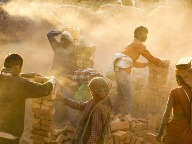 Children who work in the production of bricks, spend long hours in dust-filled environments. They carry loads of bricks on their heads and suffer from back injuries. (Photo by Narendra Shrestha/EPA)