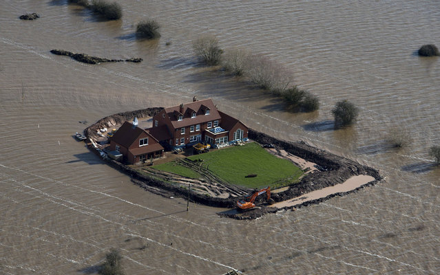 Flood waters inundate the area as one house stands alone near the flooded village of Moorland in Somerset, southwest England, Thursday February 13, 2014. The house is owned by Sam Notaro, who has built his own levee to hold back the flood waters, as the local communities face further misery in the coming days with heavy rain, wind and snow predicted to sweep across Britain. (Photo by Steve Parsons/AP Photo/PA Wire)