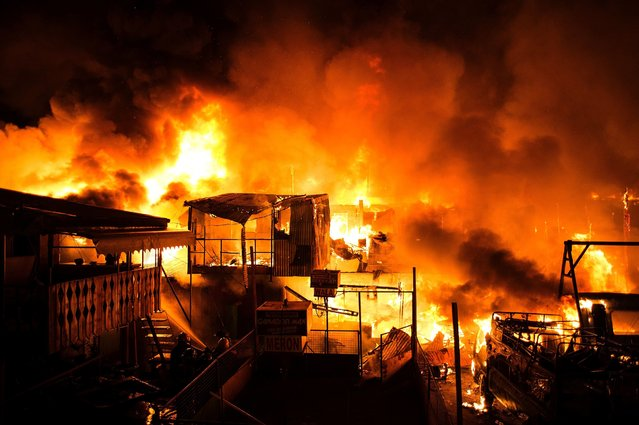 A fire burns through an informal settlers community as it burns hundreds of houses in Delpan, Tondo, Manila on February 7, 2017. (Photo by Noel Celis/AFP Photo)
