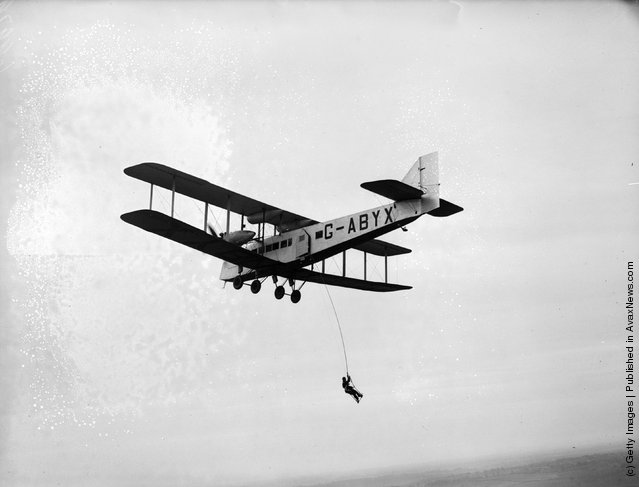 A man dangles from a rope suspended from a flying aircraft