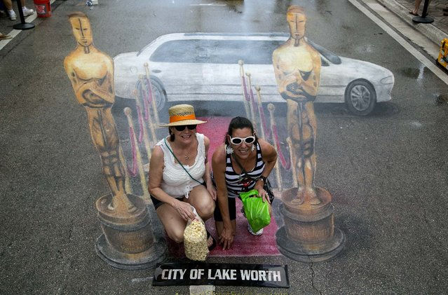 Gabrielle Mathews, of Lake Worth, and Martine Demler, of Boynton Beach, pose for photos on the red carpet of a rain soaked version of the the Academy Awards red carpet, created by artist Jennifer Chaparro. (Photo by Greg Lovett/The Palm Beach Post)