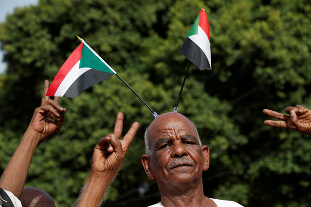 Protesters make victory signs as one of them carry Sudanese flags on his head during a demonstration in front of the Defence Ministry in Khartoum, Sudan, April 18, 2019. (Photo by Umit Bektas/Reuters)