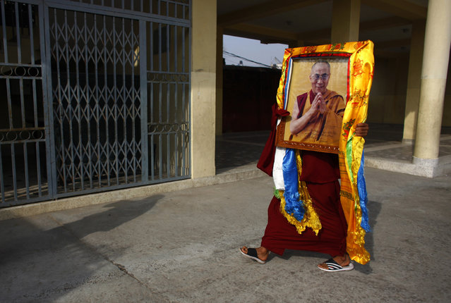 A Tibetan Monk carries a portrait of spiritual leader the Dalai Lama during festivities marking the last day of the Tibetan New Year, or Losar, in Kathmandu, Nepal, Tuesday, March 4, 2014. Tibetans across the world marked the arrival of the Wood Horse year with prayers and festivities. (Photo by Niranjan Shrestha/AP Photo)