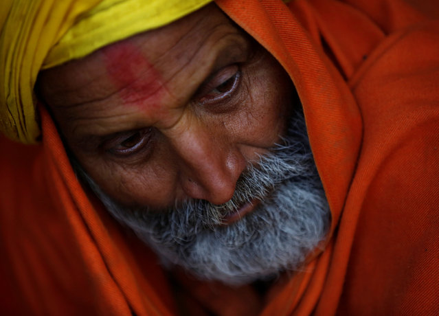 A Hindu holy man, or sadhu, covers himself with a shawl as he sits at the premises of Pashupatinath Temple, ahead of the Shivaratri festival in Kathmandu, Nepal February 21, 2017. (Photo by Navesh Chitrakar/Reuters)