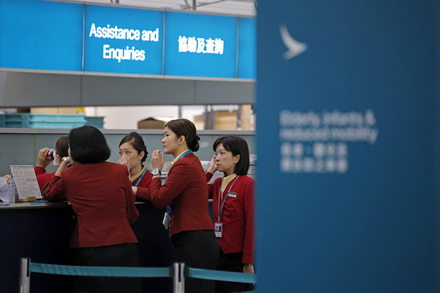 In this March 26, 2019 photo, staff members chat at the check-in counter of Cathay Pacific Airways at the Hong Kong International Airport. Cathay Pacific Airways is acquiring Hong Kong-based budget airline HK Express. Cathay said Wednesday, March 27, 2019, it will pay 4.93 billion Hong Kong dollars ($628 million) for HK Express. It said the acquisition will retain its identity as a separate brand and be operated as a low-cost carrier. (Photo by Kin Cheung/AP Photo)
