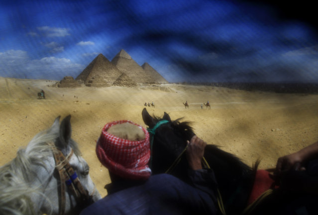 This Thursday, April 9, 2015 photo shows a man leading tourists riding horses at the historical site of the Giza Pyramids near Cairo. This photo was shot through the lowered veil of a niqab, which is worn by some conservative Muslim women. The cloth allows women to follow a strict interpretation of their religious beliefs by preventing others from seeing their faces. (Photo by Hassan Ammar/AP Photo)