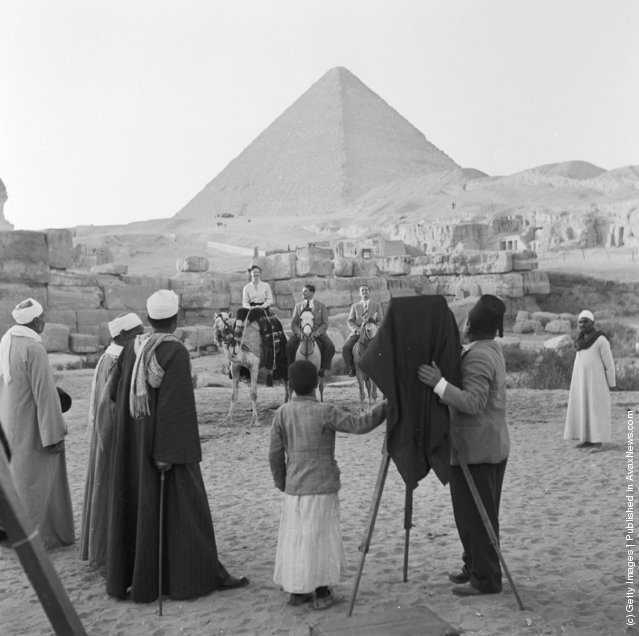 1950: A photographer taking a photograph of visitors to Giza (El Gizeh) in front of the Great Pyramid of Cheops (Khufu)