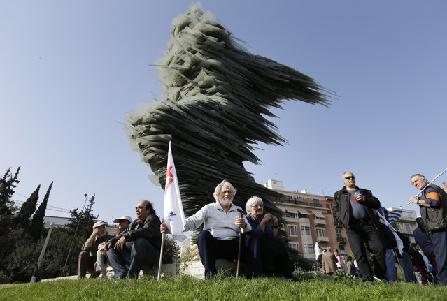 """Demonstrators sit by a 30-foot-tall sculpture of glass stacked on iron by artist Kostas Varotsos entitled """"Dromeas"""", aka """"The Runner"""", as they participate at a protest against Greece's creditors in Athens, Monday, April 4, 2016. The main sticking points are mandated pension cuts, tax reforms and future cuts Greece must make to meet bailout targets. The country has depended on bailouts since 2010. (Photo by Lefteris Pitarakis/AP Photo)"""