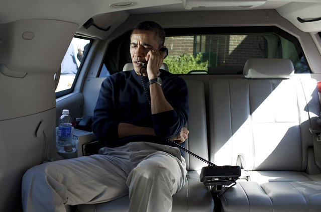 President Barack Obama talks on a phone with Afghanistan's President Hamid Karzai from his vehicle outside the Jane E. Lawton Community Center in Chevy Chase, Maryland, in this handout photograph taken and released on March 11, 2012. (Photo by Pete Souza/Reuters)