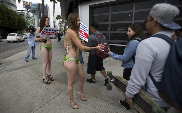 Activists Kimberly Moffatt and Meggan Anderson (2nd L) from People for the Ethical Treatment of Animals (PETA) hand out vegan hot dogs while promoting a vegan diet in Los Angeles, California May 21, 2015. (Photo by Mario Anzuoni/Reuters)