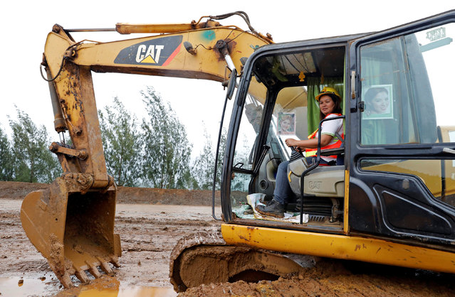 """Filipina Grace Ocol, 40, a backhoe operator, poses for a photograph in Tubay, Agusan del Sur, southern Philippines, February 16, 2017. Ocol, a mother of three, said, """"There are a few female workers that can drive big trucks and backhoe. If men can do it, why can't women do it? I'm better than the men, they can only drive trucks here but I can drive both"""". (Photo by Erik De Castro/Reuters)"""