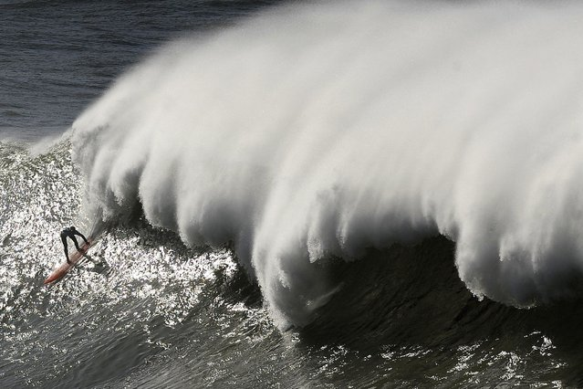 A surfer takes part in the Arnette Punta Galea Big Wave World Tour, on January 28, 2013 in the Northern Spanish Basque town of Getxo. 16 surfers took part during the five hours surf competition, riding 5 meters high waves. (Photo by Rafa Rivas/AFP Photo)