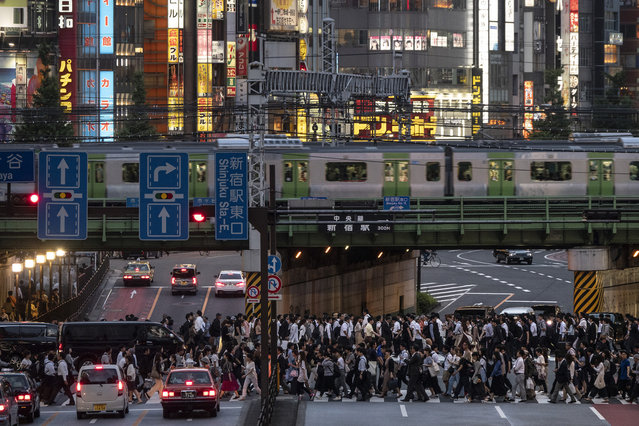 In this Tuesday, June 4, 2019, photo, a Yamanote Line train travels above commuters walking across the crossing during evening rush hours in the Shinjuku district of Tokyo. Operated by the East Japan Railway Co., the Yamanote Line in Tokyo makes a loop around the center of the city, connecting 29 stations that include key stops such as Shinjuku, Shibuya and Ikebukuro. A complete loop of about an hour offers scenes of Japanese daily lives. (Photo by Jae C. Hong/AP Photo)