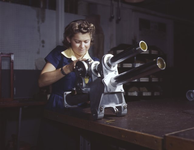 A young woman employee of North American Aviation Incorporated, working over the landing gear mechanism of a P-51 fighter plane, Inglewood, California, 1942. (Photo by Alfred T. Palmer/Buyenlarge/Getty Images)