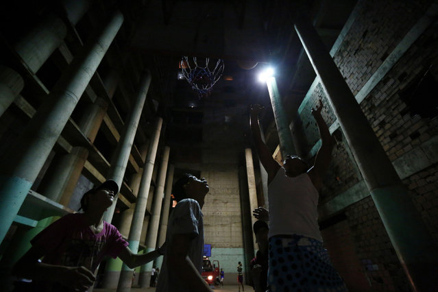 """Boys play basketball in a garage at the """"Tower of David"""" skyscraper in Caracas February 3, 2014. (Photo by Jorge Silva/Reuters)"""