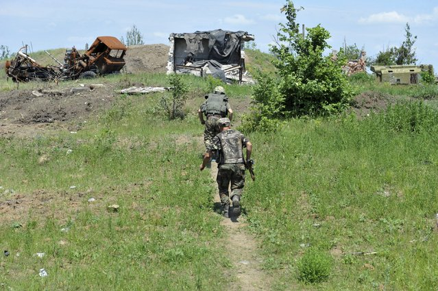 Members of the Ukrainian armed forces walk at their positions located in the village of Pisky (Pesky) near the local airport, outside Donetsk, Ukraine, June 5, 2015. REUTERS/Oleksandr Klymenko