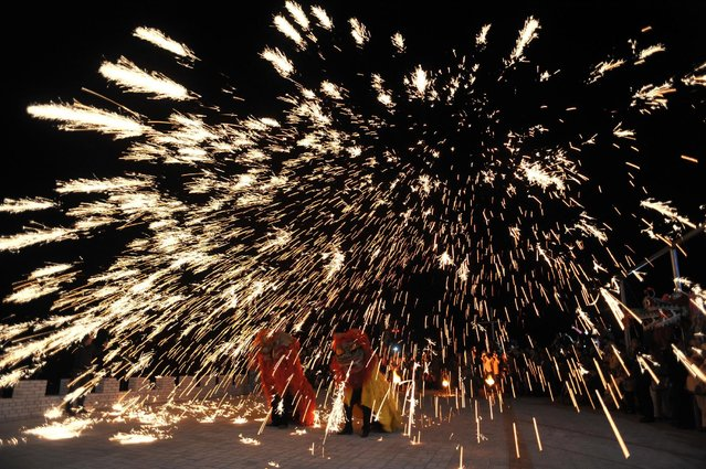 Dancers perform a lion dance under a shower of sparks from molten iron during a folk art performance in Pinglu county, Shanxi Province, China, April 24, 2016. (Photo by Reuters/China Daily)