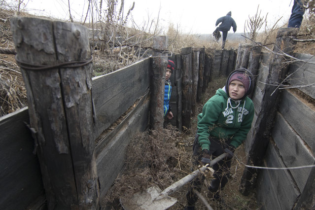 Children from an orphanage volunteer to help the city defenders to strengthen trenches on Ukraine's Army positions near the village of Rybatske 25 km from Mariupol, Ukraine, Monday, November 26, 2018. Ukrainian lawmakers were set to consider a presidential request for the introduction of martial law in the country on Monday following an incident in which Russian coast guard ships fired on Ukrainian navy vessels. (Photo by Sergey Vaganov/AP Photo)