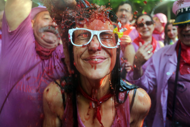 A man pours red wine on a girl's head during the Batalla del Vino (Battle of Wine) in Haro, on June 29, 2015. Every year thousands of locals and tourists climb a mountain in the northern Spanish province of La Rioja to celebrate St. Peter's day covering each other in red wine while tanker trucks filled with wine distribute the alcoholic beverage to water pistols, back mounted spraying devices, buckets which are randomly poured on heads and into any other available container. (Photo by Cesar Manso/AFP Photo)