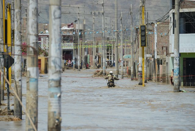 A rescue workers waits to help local residents of the town of Huarmey, 300 kilometres north of Lima, wade through muddy water on the street on March 19, 2017 after a flash flood hit the evening before. The El Nino climate phenomenon is causing muddy rivers to overflow along the entire Peruvian coast, isolating communities and neighbourhoods. Thousands have been affected since January, and 72 people have died. Most cities face water shortages as water lines have been compromised by mud and debris. (Photo by Cris Bouroncle/AFP Photo)