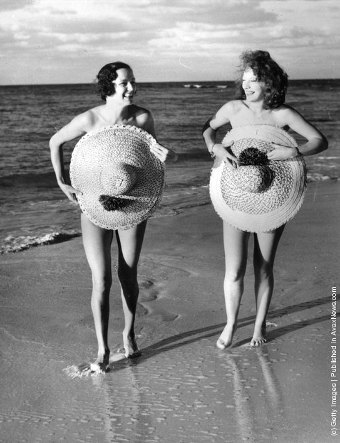 1939: Women covering up on the beach at Nassau with straw hats