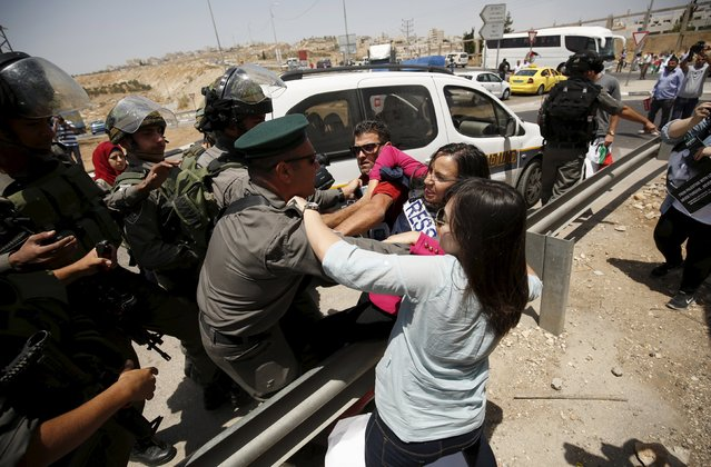 Palestinian journalists scuffle with Israeli border policemen during a protest marking the first anniversary of the killing of 16-year-old Palestinian Mohammed Abu Khudair, who was burnt in Jerusalem in a suspected revenge attack for the kidnapping and slaying of three Israeli teens last year, near the West Bank city of Ramallah July 2, 2015. (Photo by Mohamad Torokman/Reuters)