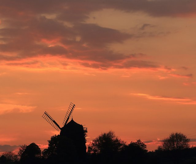 A traditional windmill is silhouetted against the sky during sunset in Niederndodeleben, Germany, 22 April 2014. The windmill dated from the 19th century is no longer in use as a mill but was rebuild as a holiday flat. (Photo by Jens Wolf/EPA)