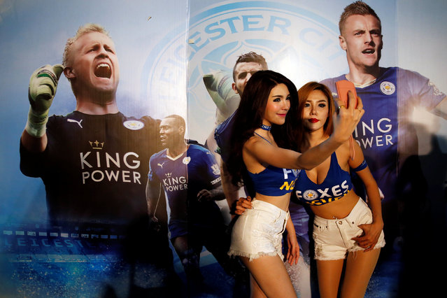 Leicester City hostesses take pictures in front of a billboard as people gather to watch the team's English Premier League soccer match against Everton on a big screen, in Bangkok, Thailand, May 7, 2016. (Photo by Jorge Silva/Reuters)