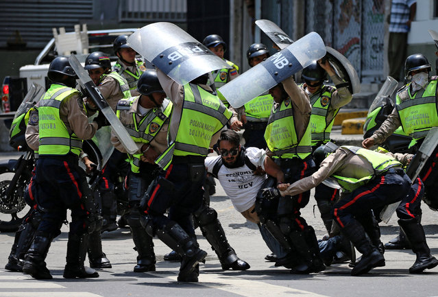 A demonstrator is arrested by riot police while rallying against Venezuela's President Nicolas Maduro's government in Caracas, Venezuela April 10, 2017. (Photo by Carlos Garcia Rawlins/Reuters)