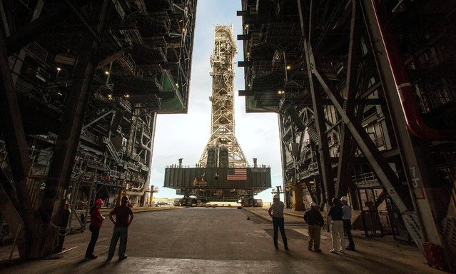 NASA employees look on as the Artemis launch tower rolls back from Pad 39B inside Bay 3 of the Vehicle Assembly Building (VAB) at the Kennedy Space Center in preparation for the landfall of Hurricane Dorian, in Cape Canaveral, Florida, U.S., August 30, 2019. (Photo by Steve Nesius/Reuters)
