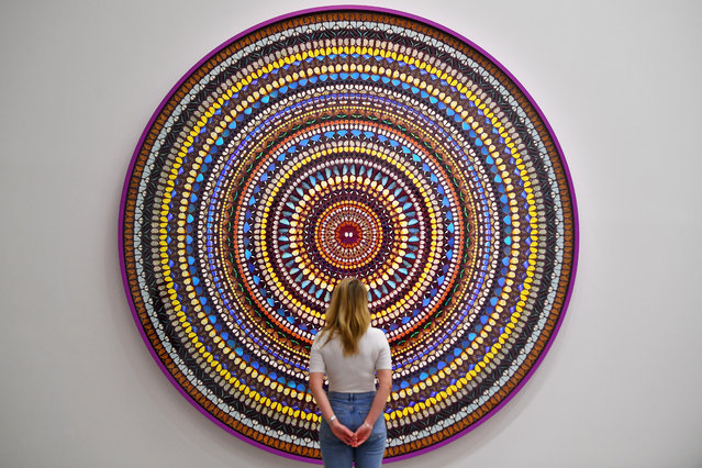 """A gallery assistant poses in front of """"Deity"""" by Damien Hirst during an exhibition of his new work entitled """"Mandalas"""" at the White Cube in London, Britain, September 19, 2019. (Photo by Dylan Martinez/Reuters)"""