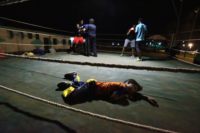 A boy sleeps inside the ring as Arafat Abkar (2nd R) , 22, practises boxing at Nile Club in Khartoum May 9, 2016. (Photo by Mohamed Nureldin Abdallah/Reuters)