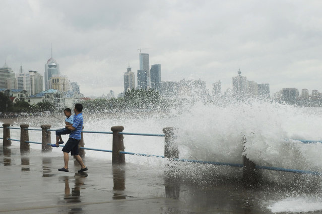 A man carrying a child runs away from massive waves hit the seacoast of Qingdao in east China's Shandong province Sunday, July 12, 2015. A typhoon pounded the Chinese coast south of Shanghai on Saturday with strong winds and heavy rainfall, submerging roads, felling trees and forcing the evacuation of people. (Photo by Chinatopix via AP Photo)