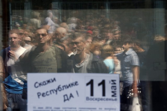 "Ukrainian people reflected in the a window with a banner reading ""Say Republic yes – 11 May"" stand in line for voting at a polling station in Donetsk, Ukraine, 11 May 2014. Residents of eastern Ukraine began voting on an independence referendum that was organized by pro-Russian separatists and rejected by the government in Kiev. (Photo by Maxim Shipenkov/EPA)"