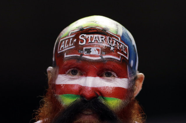 A fan watches from the stands during the fifth inning of the MLB All-Star baseball game, Tuesday, July 14, 2015, in Cincinnati. (Photo by Jeff Roberson/AP Photo)