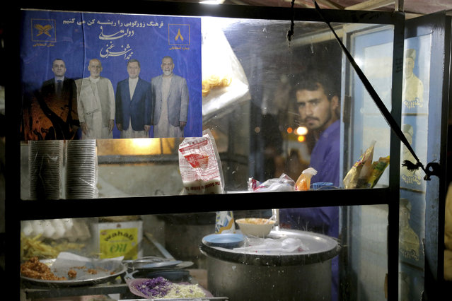 In this Monday, September 23, 2019 photo, a poster of presidential candidate Ashraf Ghani and members of his party hangs in the window of a shop on the outskirts of Kabul, Afghanistan. (Photo by Ebrahim Noroozi/AP Photo)