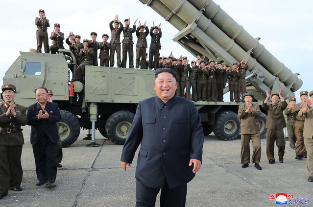 """This Saturday, August 24, 2019, photo provided Sunday, Aug. 25, by the North Korean government, shows North Korean leader Kim Jong Un, center, smiles after the test firing of an unspecified missile at an undisclosed location in North Korea. North Korea fired two suspected short-range ballistic missiles off its east coast on Saturday in the seventh weapons launch in a month, South Korea's military said, a day after it vowed to remain America's biggest threat in protest of U.S.-led sanctions on the country. The content of this image is as provided and cannot be independently verified. Korean language watermark on image as provided by source reads: """"KCNA"""" which is the abbreviation for Korean Central News Agency. (Photo by Korean Central News Agency/Korea News Service via AP Photo)"""