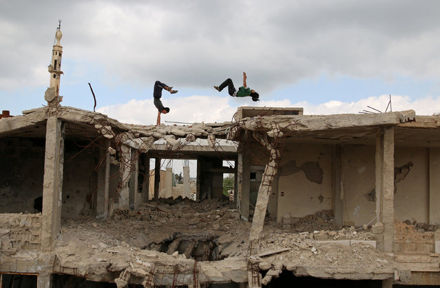 Parkour coach Ibrahim al-Kadiri (R), 19, and Muhannad al-Kadiri, 18, demonstrate their Parkour skills amid damaged buildings in the rebel-held city of Inkhil, west of Deraa, Syria, April 7, 2017. Ibrahim discovered Parkour in Jordan, where he had fled to escape the war. Back in his home town since 2015, he now leads a group of 15 practitioners. (Photo by Alaa Al-Faqir/Reuters)