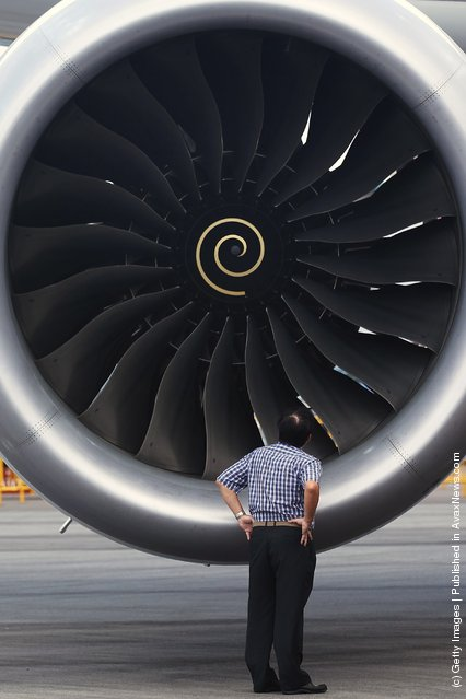A man looks into the Rolls Royce engine of the   Boeing 787 Dreamliner