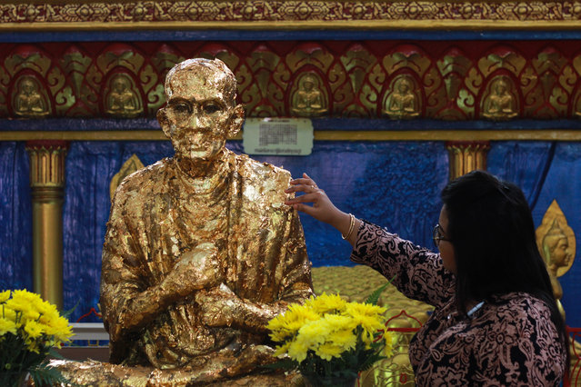 A devotee put a golden paper  onto  Buddha statue during Vesak day in Penang, Malaysia, on May 10,2017. Buddhists around the world have celebrate Vesak ,one of the most important day in Buddhist calendar informally known as Buddha 's birthday, it commemorates the birth, enlightenment and the death of Buddha, Siddhartha Gautama.Buddhist scriptures state that each occurred on the full moon of the Indian lunar month of Vesakha.Buddhists celebrate Vesak every year on the day of full moon in May. (Photo by Shaiful Azre/NurPhoto via Getty Images)