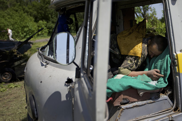 A body seen in a destroyed car near the village of Blahodatne, eastern Ukraine, on Thursday, May 22, 2014. At least 11 Ukrainian troops were killed and about 30 others were wounded when Pro-Russians attacked a military checkpoint, the deadliest raid in the weeks of fighting in eastern Ukraine. Three charred Ukrainian armored infantry vehicles, their turrets blown away by powerful explosions, and several burned vehicles stood at the site of the combat. (Photo by Ivan Sekretarev/AP Photo)