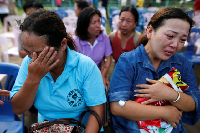 Malawian Saw-wa, 33, (L) and Yupin Saw-wa, 28 who lost their daughters, cry near a burnt building at the Pitakkiat Wittaya School in the northern province of Chiang Rai, Thailand, May 23, 2016. (Photo by Athit Perawongmetha/Reuters)